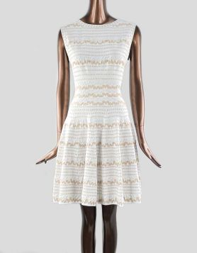 Alaïa sleeveless, scoop-neck A-line mini dress in cream with tan abstract design throughout. V-neck in back with concealed zipper.