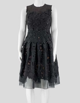 Carmen Marc Valvo black embroidery and floral appliqué sleeveless dress with a pleated skirt and semi-sheer accents at the top and at the hem. Size 6 US